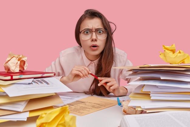 Close up de uma jovem e inteligente secretária descontente com uma expressão intrigada, usando óculos grandes, estudando documentos e termos de contrato