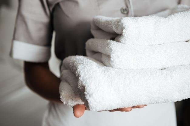 Close-up de uma jovem empregada segurando toalhas dobradas