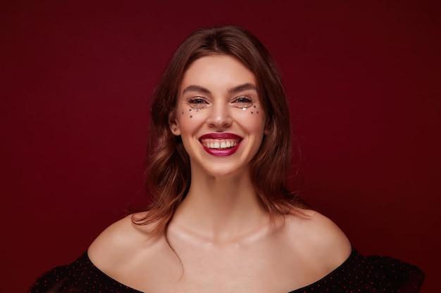 Close-up de uma jovem encantadora de cabelos castanhos com penteado ondulado, maquiagem de noite com pequenas estrelas no rosto, sorrindo amplamente para a câmera enquanto posava sobre um fundo de clarete