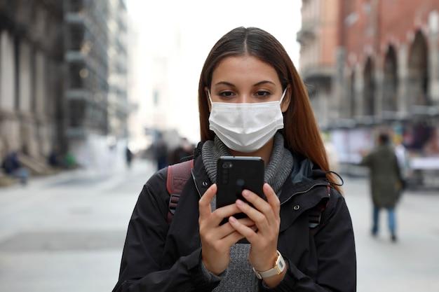 Close-up de uma jovem estudante universitária usando máscara cirúrgica e usando seu telefone celular em uma rua da cidade