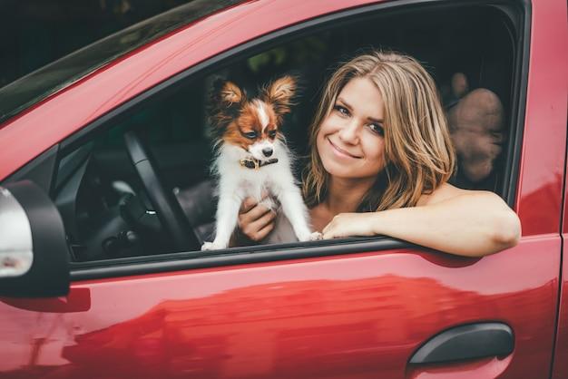 Close-up de uma jovem garota e um cachorro vermelho branco no carro.