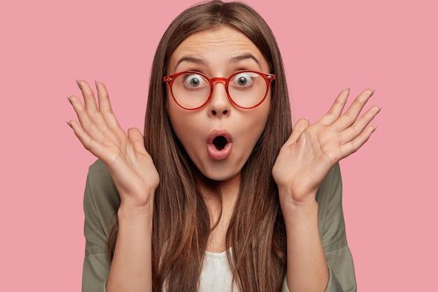 Close up de uma jovem incrível surpresa com os olhos arregalados e cruzando as mãos perto do rosto