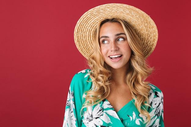 Close-up de uma jovem loira atraente com vestido de verão e chapéu de palha em pé, isolado sobre uma parede rosa, olhando para longe