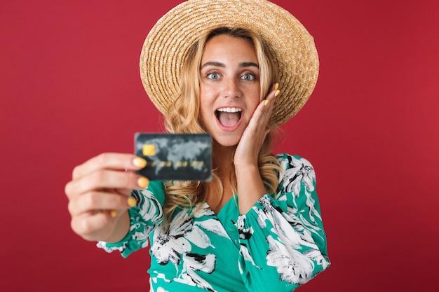 Close-up de uma jovem loira atraente e animada com vestido de verão e chapéu de palha em pé, isolado sobre uma parede rosa, mostrando o cartão de crédito