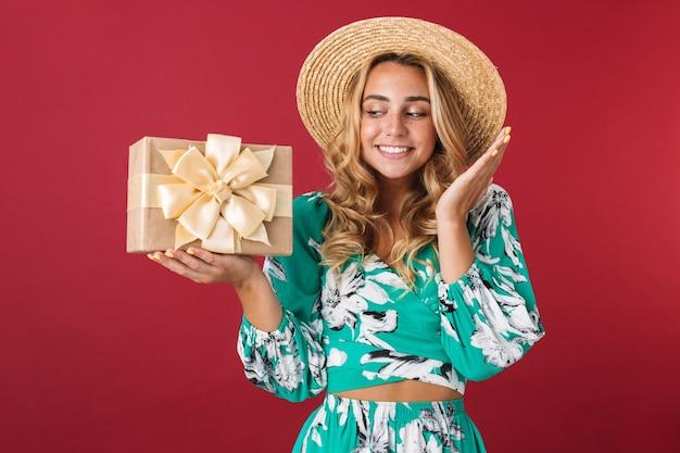 Close-up de uma jovem loira atraente e feliz usando um vestido de verão e chapéu de palha em pé, isolado sobre uma parede rosa, mostrando a caixa de presente