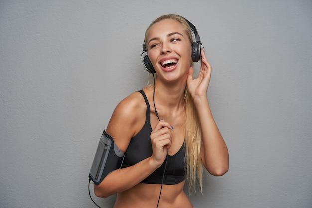 Close-up de uma jovem loira de cabelos compridos feliz curtindo música em seus fones de ouvido e olhando alegremente para o lado com um largo sorriso, vestida com uma blusa esportiva preta enquanto posava sobre um fundo cinza claro