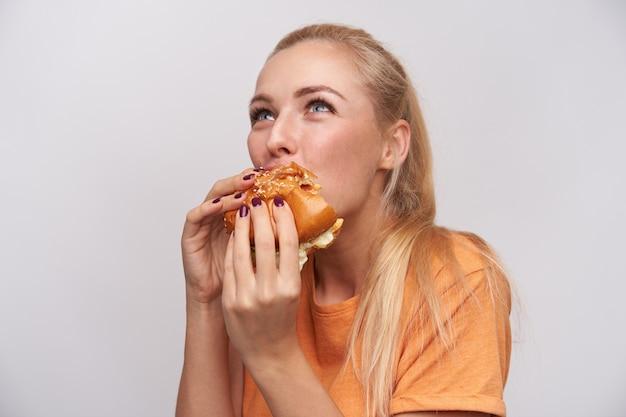 Close-up de uma jovem loira de olhos azuis com penteado casual, segurando um grande hambúrguer saboroso nas mãos e mordendo avidamente um pedaço, de pé contra um fundo branco