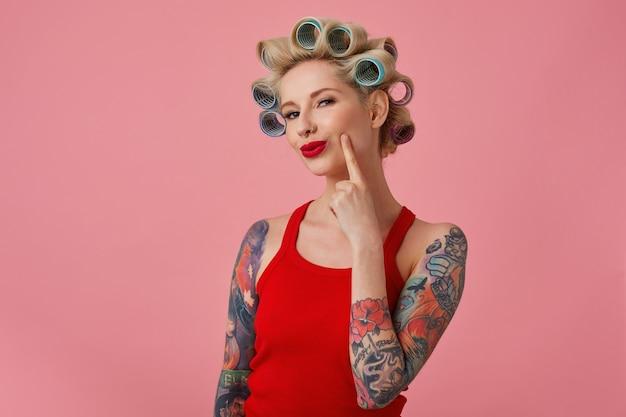 Close-up de uma jovem loira tatuada com rolos na cabeça e lábios vermelhos olhando astutamente para a câmera e sorrindo levemente, vestida com roupas casuais, em pé sobre um fundo rosa