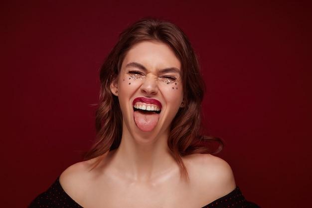 Close-up de uma jovem morena alegre e animada com estrelas de prata no rosto, mostrando a língua e apertando os olhos, posando em cima com os ombros abertos