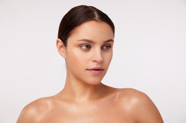 Close-up de uma jovem morena encantadora usando maquiagem natural e penteado casual enquanto posa, olhando para o lado com o rosto calmo