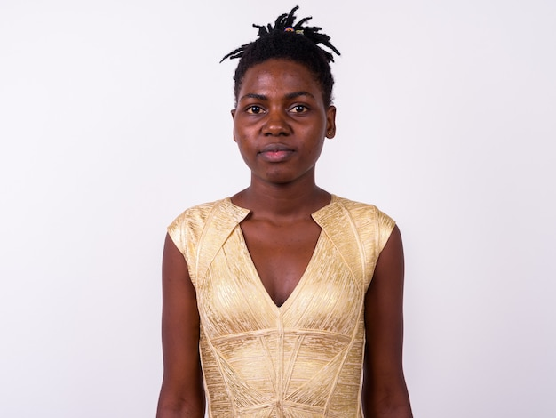 Close-up de uma jovem mulher africana com um vestido dourado pronto para a festa, isolada