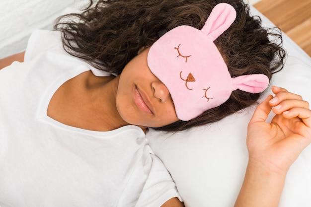 Close-up de uma jovem mulher afro-americana cansada, dormindo na cama