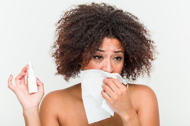 Close-up de uma jovem mulher afro-americana usando um spray nasal