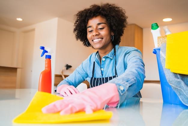 Close-up de uma jovem mulher afro fazendo limpeza na nova casa