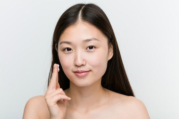 Close-up de uma jovem mulher asiática bonita e natural, aplicar um creme hidratante