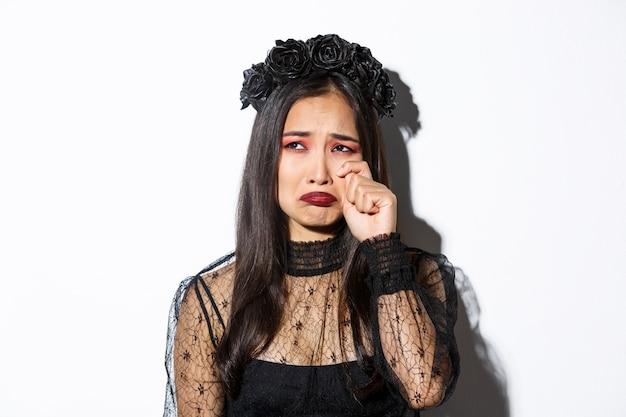 Close-up de uma jovem mulher asiática fantasiada de bruxa, chorando e parecendo miserável, triste, em pé sobre um fundo branco.