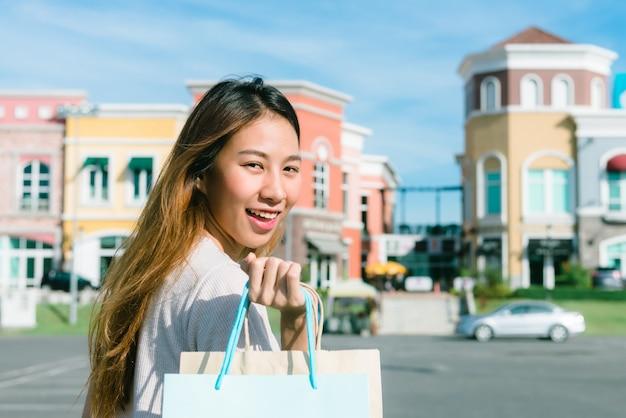 Close up de uma jovem mulher asiática, fazer compras um mercado de pulgas ao ar livre com um fundo de pastel buliding