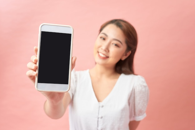Close-up de uma jovem mulher asiática mostrando um celular com tela em branco em pé e olhando para a câmera sobre o rosa