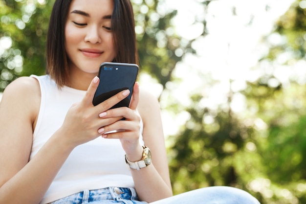 Close-up de uma jovem mulher asiática usando um telefone celular enquanto está sentado no parque