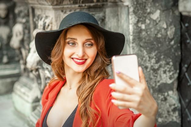 Close-up de uma jovem mulher caucasiana tomando selfie no smartphone em pé e sorrindo contra um prédio antigo ao ar livre