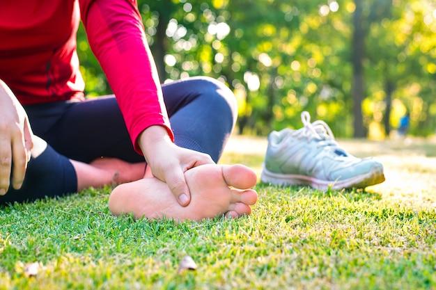 Close-up de uma jovem mulher de esportes asiáticos com dor nos músculos e articulações durante exercícios ao ar livre, durante o treinamento ou corrida e conceito de lesão esportiva