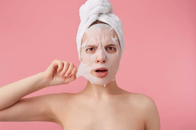 Close-up de uma jovem mulher desconectada com uma toalha na cabeça após o banho, tentando remover a máscara de tecido do rosto, fica de pé.