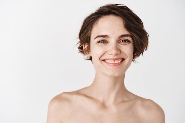 Close-up de uma jovem mulher feliz com pele pálida e sem maquiagem, em pé seminua na parede branca, sorrindo e parecendo feliz. conceito de cuidados com a pele e beleza feminina