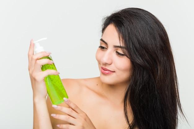 Close-up de uma jovem mulher hispânica bonita e natural, segurando uma garrafa de aloe vera