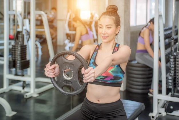 Close up de uma jovem mulher muscular que levanta peso no gym.