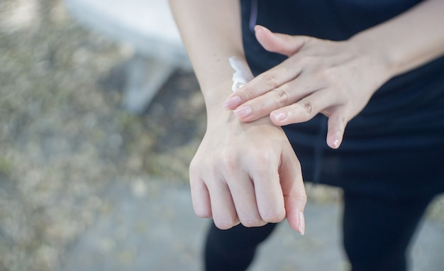 Close up de uma jovem mulher que aplica a proteção solar a seu braço.