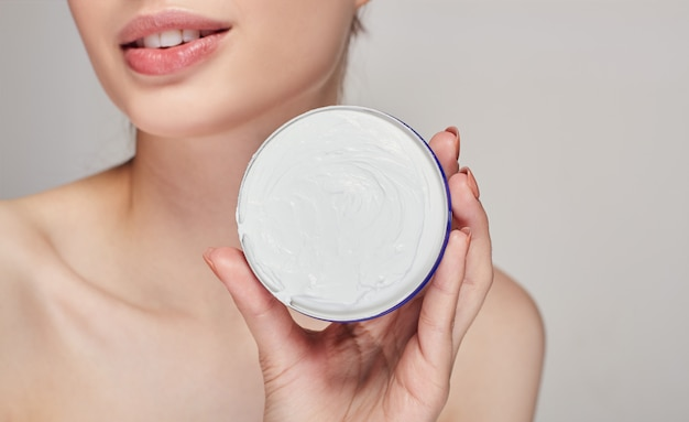 Close-up de uma jovem mulher, segurando um pote aberto de creme nas mãos dela. spa e beleza. cuidados com a pele.