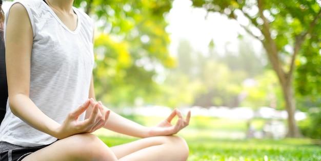 Close up de uma jovem praticando yoga sentar na grama verde no parque natural da manh