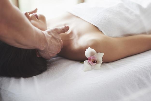 Close-up de uma jovem recebe uma massagem no salão de beleza. procedimentos para pele e corpo.