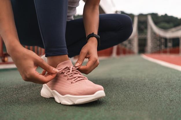 Close-up de uma jovem se preparando para correr ao ar livre enquanto amarra seus tênis rosa