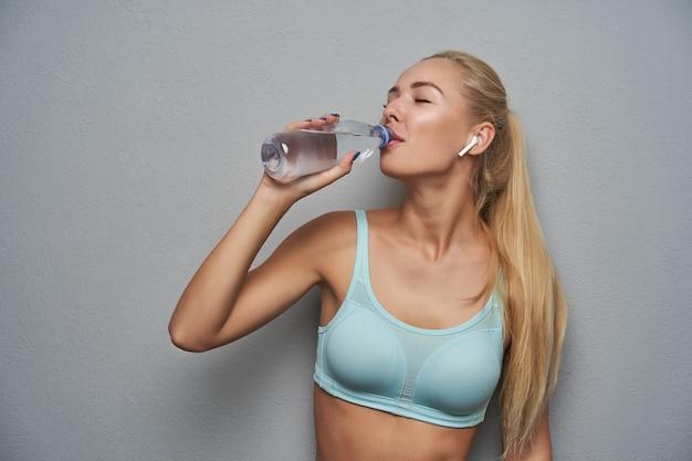 Close-up de uma jovem senhora loira saudável bebendo água com os olhos fechados enquanto posava sobre um fundo cinza, cansada após o treino matinal, vestindo blusa esportiva mint