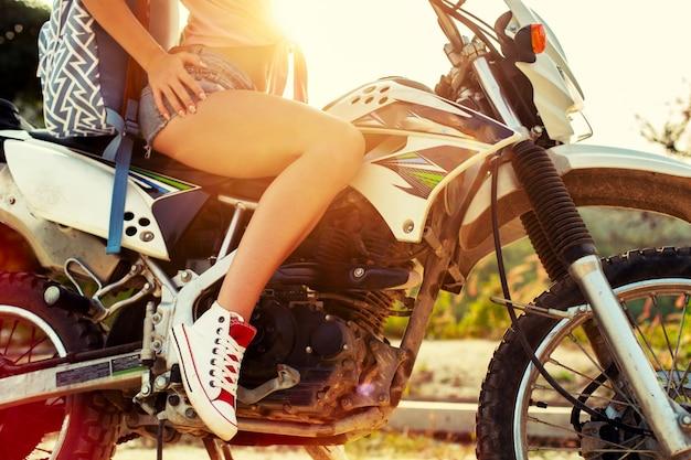 Close-up de uma jovem sentada em uma motocicleta no verão