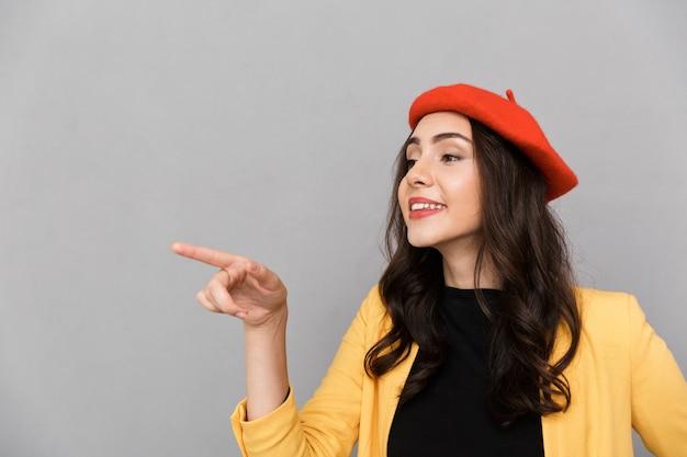 Close-up de uma jovem sorridente com chapéu vermelho em pé sobre um fundo cinza, apontando o dedo para o espaço da cópia