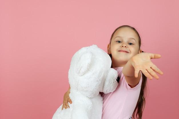 Close-up de uma linda garota charmosa abraça um ursinho de pelúcia branco e acena para nós