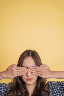 Close-up de uma linda garota com cabelo comprido fechando os olhos com as duas mãos com copyspace