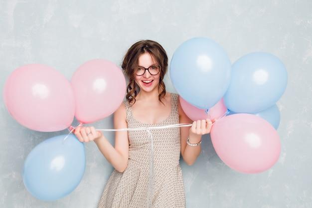 Close-up de uma linda garota morena de pé em um estúdio, sorrindo amplamente e brincando com balões azuis e rosa. ela esta se divertindo