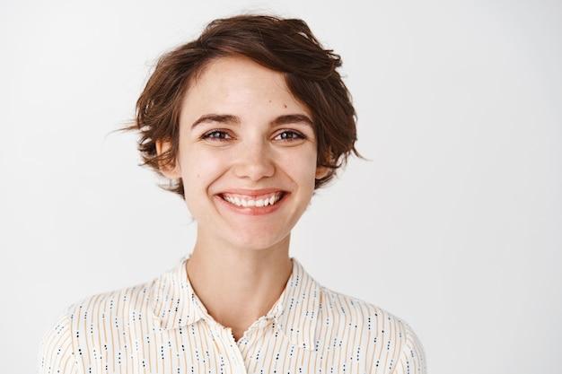 Close-up de uma linda garota natural sorrindo com dentes brancos, parecendo feliz e animada em pé na parede branca