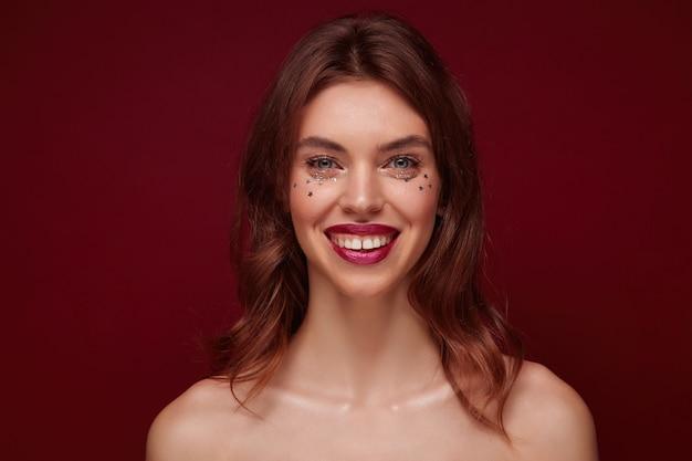 Close-up de uma linda jovem morena feliz com maquiagem de noite, olhando alegremente para a câmera com um sorriso encantador, mostrando seus dentes brancos perfeitos em pé sobre um fundo de clarete