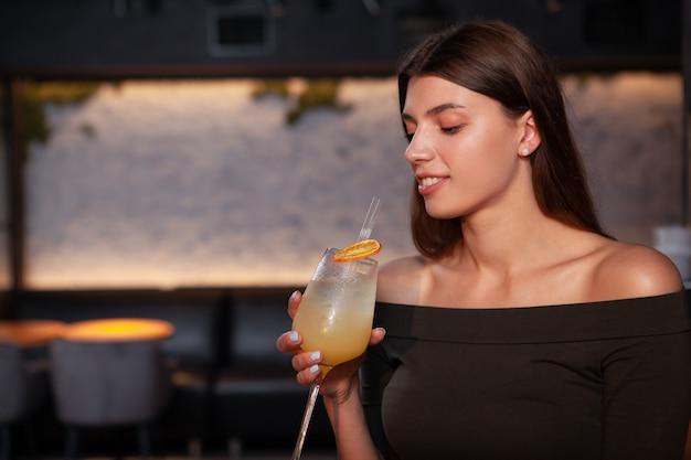 Close-up de uma linda mulher elegante com um cocktail no bar à noite, copie o espaço