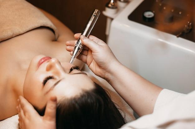 Close-up de uma linda mulher fazendo procedimentos de radiofrequência no rosto por um cosmetologista em um centro de bem-estar.