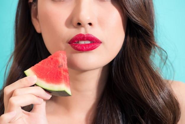 Close-up de uma linda mulher segurando uma fatia de melancia com lábios vermelhos.