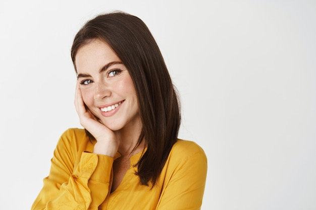 Close-up de uma linda mulher sorridente, parecendo sedutora para a câmera, tocando a bochecha e corando, em pé na parede branca com uma camisa amarela