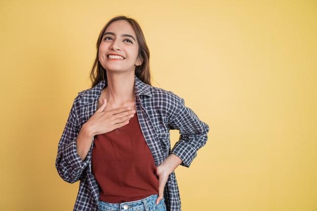 Close-up de uma linda mulher sorrindo com as mãos na frente do peito e uma expressão calma com copyspace