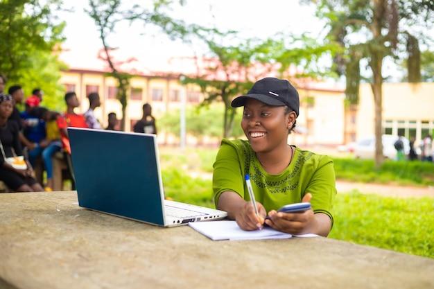 Close-up de uma linda senhora africana estudando no campus da escola, sentindo-se animada
