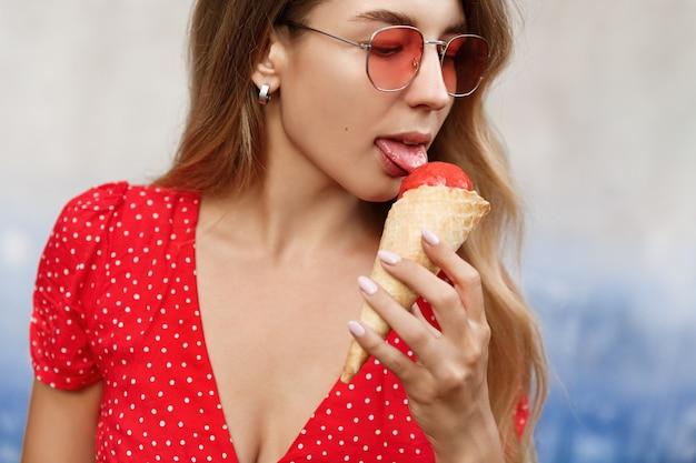 Close-up de uma loira fascinante lambendo sorvete perto da parede da rua