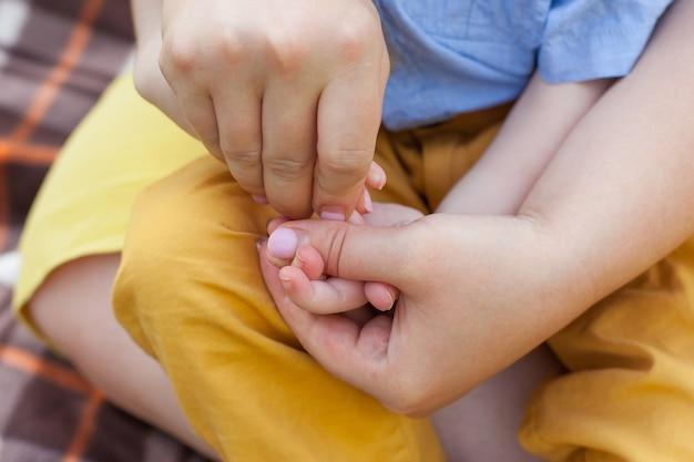 Close-up de uma mãe fazendo massagem nas mãos de um menino deficiente. crianças deficientes. inclusividade